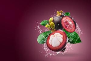 Wasser spritzt auf Mangostanfrüchten foto