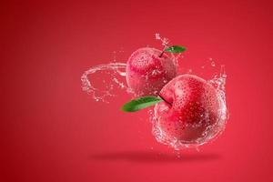 Wasser spritzt auf frischen roten Apfel foto