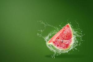 Wasser spritzt auf eine Scheibe Wassermelone