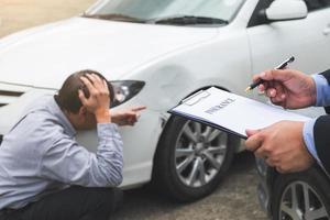 Versicherungsvertreter, der an einem Bericht über einen Autounfall arbeitet foto