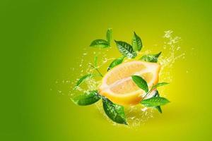 Wasser spritzt auf Zitronen und grünem Teeblatt foto