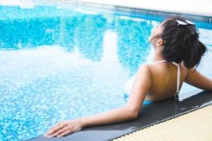 glücklicher Frauenlebensstil, der im Luxusschwimmbad entspannt foto