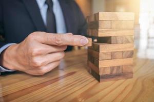 Unternehmer, der Holzblock auf Turm setzt und zieht
