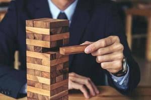 Hand der Geschäftsperson, die Holzblock auf Turm setzt