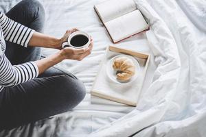 junge Frau auf dem Bett mit altem Buch und morgendlicher Tasse Kaffee