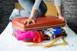 Frau packt Kleidung in Koffer foto