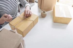 junge Verkäuferin, die Paket vorbereitet