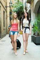 zwei fröhliche Mädchen mit Gepäck