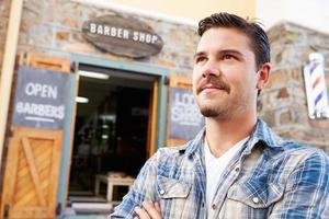 Porträt des Hipster-Friseurs, der außerhalb des Geschäfts steht foto