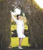 junge glückliche Braut, die unter Bogen aufwirft. foto