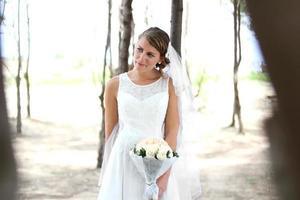 schöne Braut, die einen Blumenstrauß hält foto