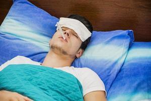 junger Mann im Bett, der Fieber mit Thermometer misst