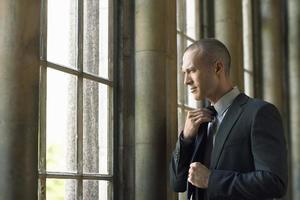 Geschäftsmann, der Krawatte anpasst foto