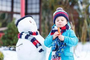 lustiger Junge, der einen Schneemann im Winter im Freien macht foto