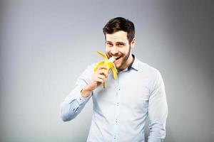 Porträt eines klugen ernsten jungen Mannes, der Banane isst foto