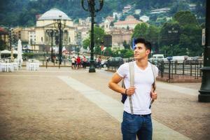schöner junger Mann, der im europäischen Stadtplatz geht foto