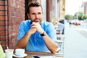 junger Mann, der im Straßencafé wartet foto