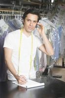 Mann auf Abruf beim Schreiben eines Notizblocks in der Wäsche foto