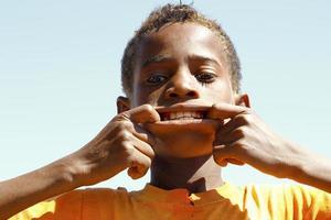 Foto des entzückenden jungen glücklichen Jungen, der Kamera betrachtet.