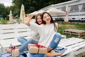 zwei schöne Mädchen sitzen auf einer Bank foto