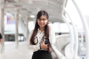 glückliche Geschäftsfrau, die auf Bürgersteig steht. foto