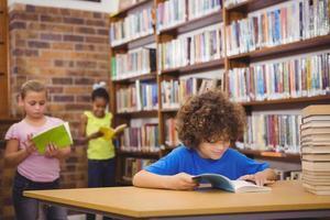glücklicher Schüler, der ein Bibliotheksbuch liest foto