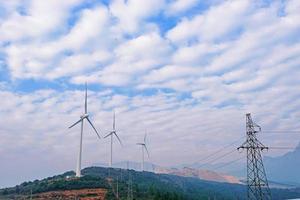 rotierende Windkraftanlage vor bewölktem Himmel foto