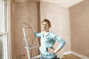 Frau, die Kratzwerkzeug im nicht renovierten Raum hält