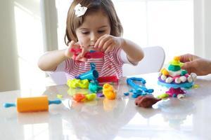 Mädchen spielt mit Spielteig foto