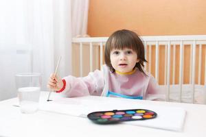 reizender kleiner Junge, der mit Aquarellfarben zu Hause malt foto