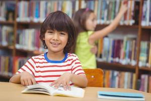 Schüler lächelt in der Kamera in der Bibliothek foto