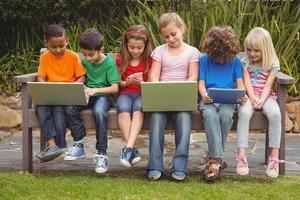 Kinder sitzen auf einer Parkbank foto