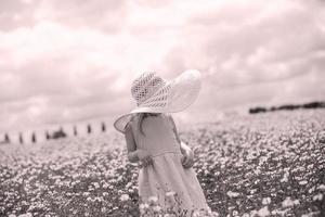 kleines Mädchen in einem Blumenfeld foto