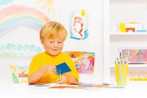 blonder kleiner Junge, der Pappform in der Klasse schneidet foto