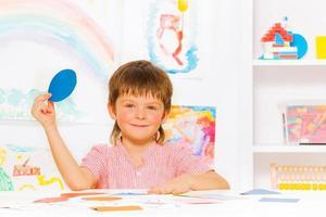 glücklicher kleiner Junge, der Formen im Kindergarten lernt foto