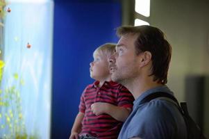 Vater und sein Sohn genießen die Aussicht auf das Unterwasserleben foto