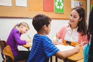 glückliche Lehrerin, die ihren Schülern hilft foto