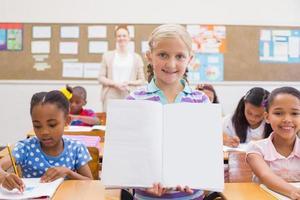 niedlicher Schüler, der während der Klassenpräsentation in die Kamera lächelt foto