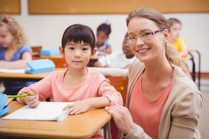 hübscher Lehrer, der Schüler im Klassenzimmer hilft, in Kamera zu lächeln foto