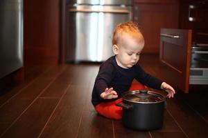 Baby spielt mit einem Topf in einer Küche foto