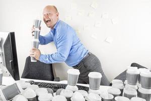 glücklicher Geschäftsmann trinkt zu viel Kaffee foto
