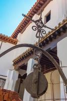 alte Riemenscheibe eines Brunnens in einem spanischen Hof foto