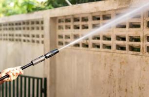 Frau Reinigung waill mit Hochdruckwasserstrahl foto