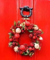 festlicher Weihnachtskranz, der an der roten Tür hängt foto