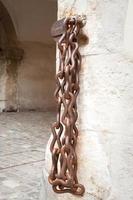 rostige Eisenkette, die an Backsteinmauer des historischen Gebäudes hängt foto