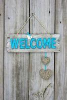 Willkommensschild mit Seilherzen, die an Holztür hängen foto