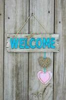 Willkommensschild mit Herzen, die auf Holzhintergrund hängen