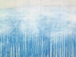 blau verschüttete Farbe auf der rissigen weißen Fassade