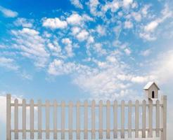 weißer Zaun mit Vogelhaus und blauem Himmel foto