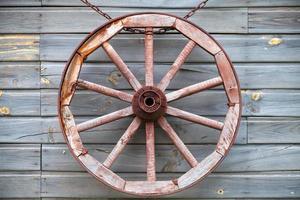 altes gebrauchtes Holzrad, das an ländlicher Wand hängt foto
